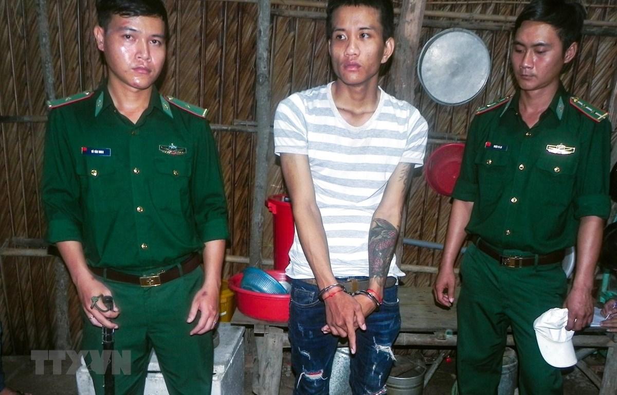 Trong ảnh: Đối tượng Kim Hoàng Thạch bị bắt cùng tang vật. (Ảnh: Trung Hiếu/TTXVN)