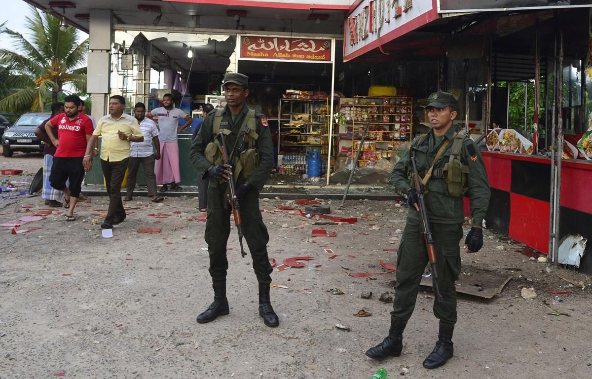 Lực lượng an ninh Sri Lanka gác bên ngoài một cửa hàng bị đập phá trong vụ đụng độ nhằm vào người Hồi giáo ở Minuwangoda ngày 14/5. (Ảnh: AFP/TTXVN)