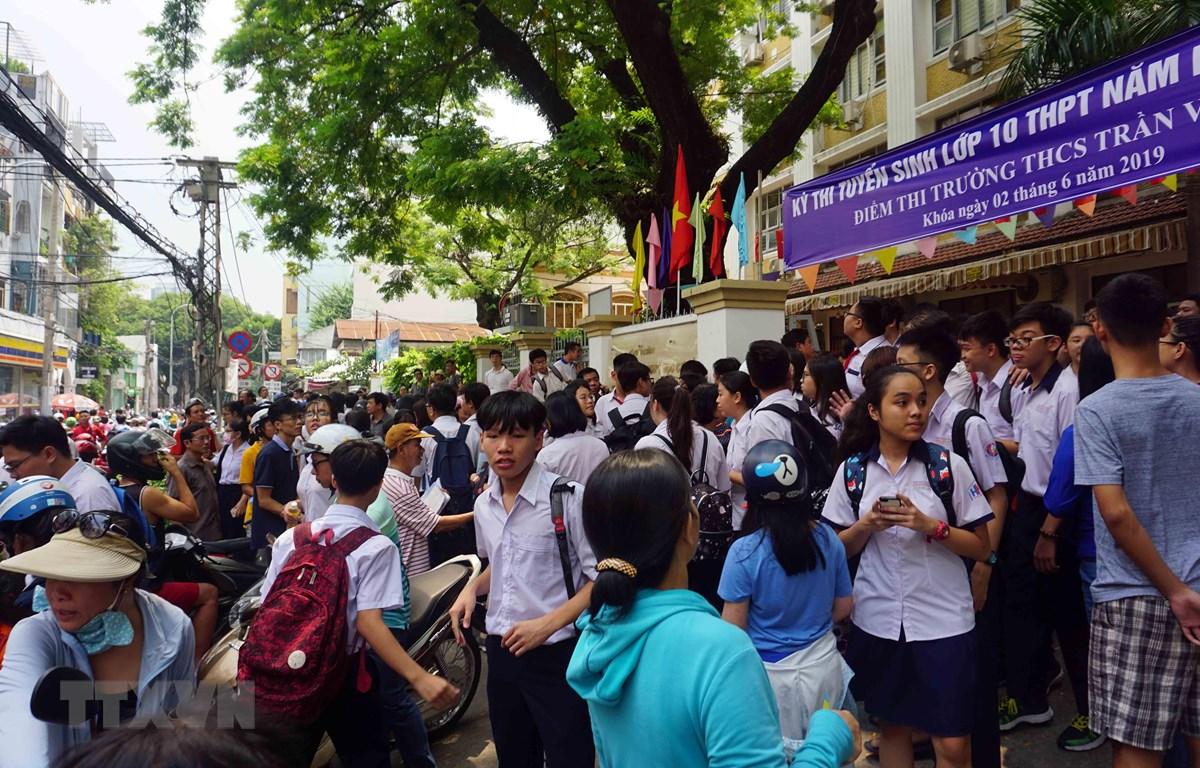Nhiều phụ huynh đứng chờ con em tại điểm thi Trường Trung học cơ sở Trần Văn Ơn (Quận 1). (Ảnh: Thu Hoài/TTXVN)
