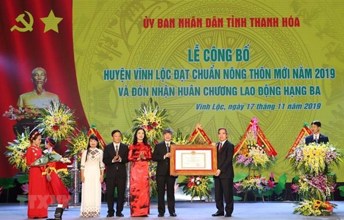 Đồng chí Nguyễn Văn Bình Trưởng ban Kinh tế Trung ương trao Bằng công nhân huyện Vĩnh Lộc đạt chuẩn huyện nông thôn mới năm 2019. (Ảnh: Duy Hưng/TTXVN)