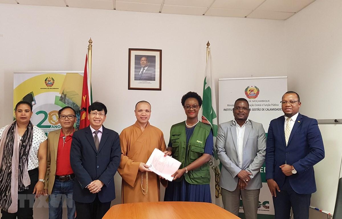 Thượng tọa Thích Đồng Huệ trao các văn bản liên quan đến lô hàng cứu trợ cho Tổng Giám đốc Cơ quan Quản lý thiên tai Mozambique Augusta Maíta. (Ảnh: Đình Lượng/TTXVN)