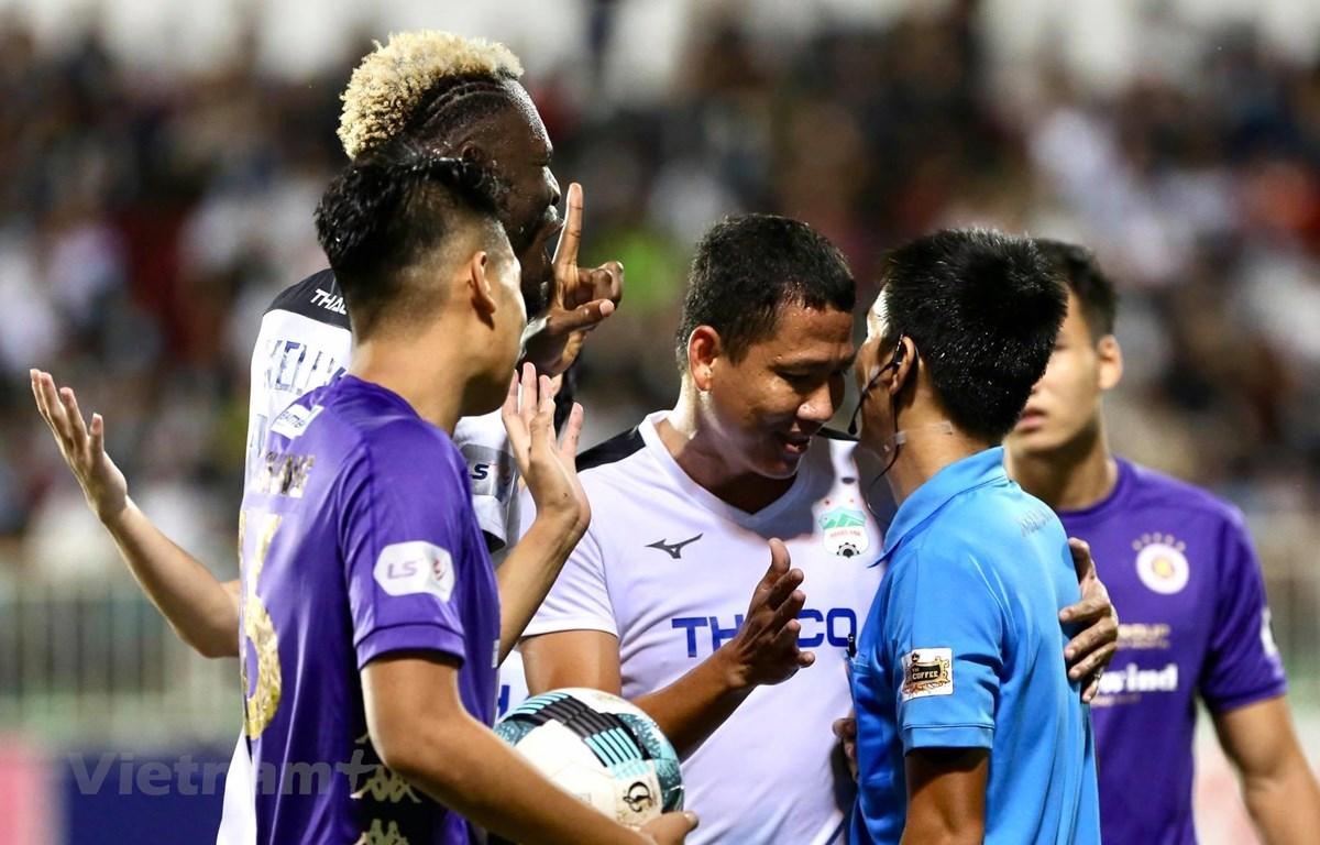 Anh Đức can ngăn đồng đội phản ứng gay gắt để một mình nói chuyện bình tĩnh với trọng tài sau quyết định từ chối phạt đề cho Hoàng Anh Gia Lai. (Ảnh: Huệ Thu/Vietnam+)