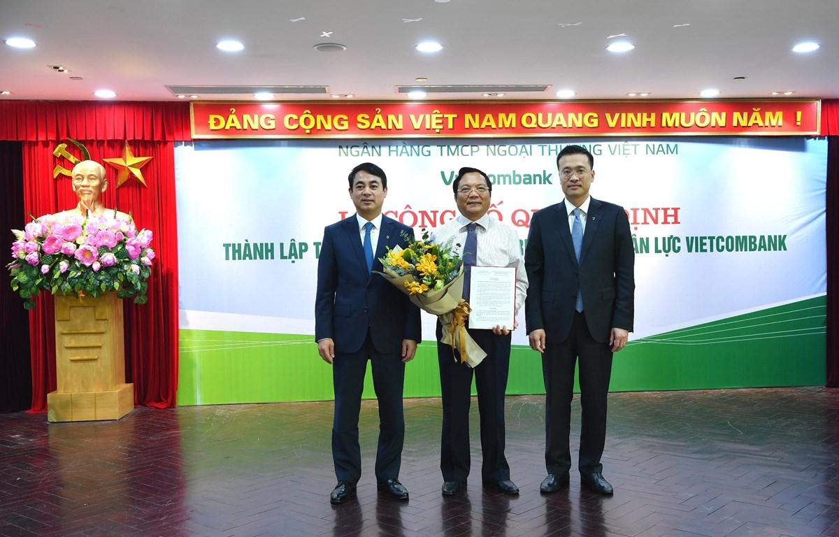 Lãnh đạo Vietcombank trao quyết định và tặng hoa cho ông Kiều Hữu Thiện, tân Giám đốc Trường Đào tạo Vietcombank. (Ảnh: CTV/Vietnam+)