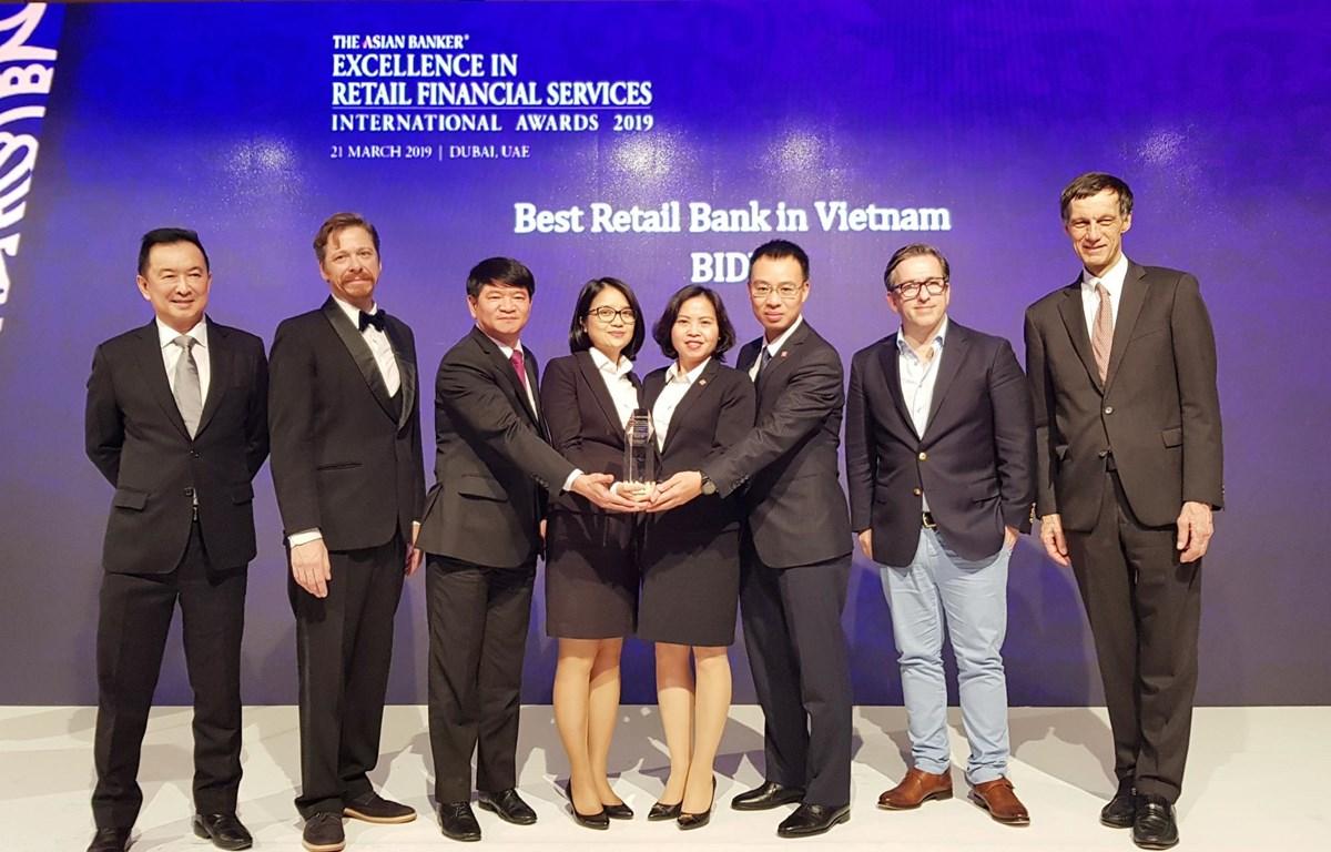 Lãnh đạo BIDV nhận giải thưởng từ ban tổ chức. (Ảnh: CTV/Vietnam+)
