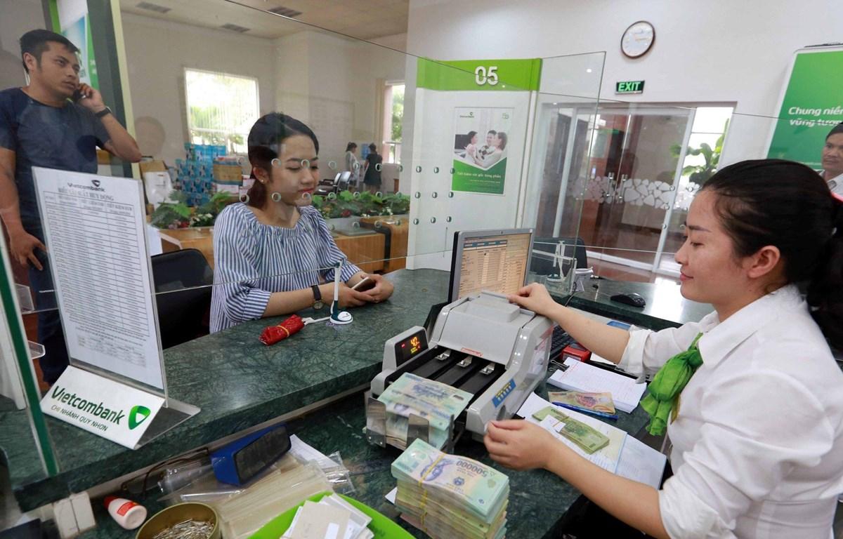 Giao dịch tại ngân hàng. (Ảnh: CTV/Vietnam+)