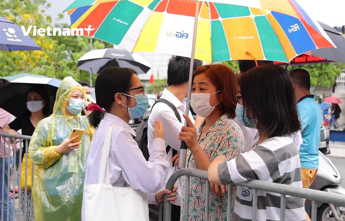 Học sinh chia sẻ niềm vui với người thân (Ảnh: Hoàng Đạt/Vietnam+)