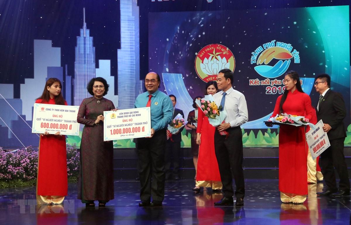 Chủ tịch Ủy ban MTTQ Việt Nam Thành phố Hồ Chí Minh Tô Thị Bích Châu tiếp nhận tượng trưng số tiền ủng hộ từ các nhà hảo tâm. (Ảnh: Xuân Khu/TTXVN)