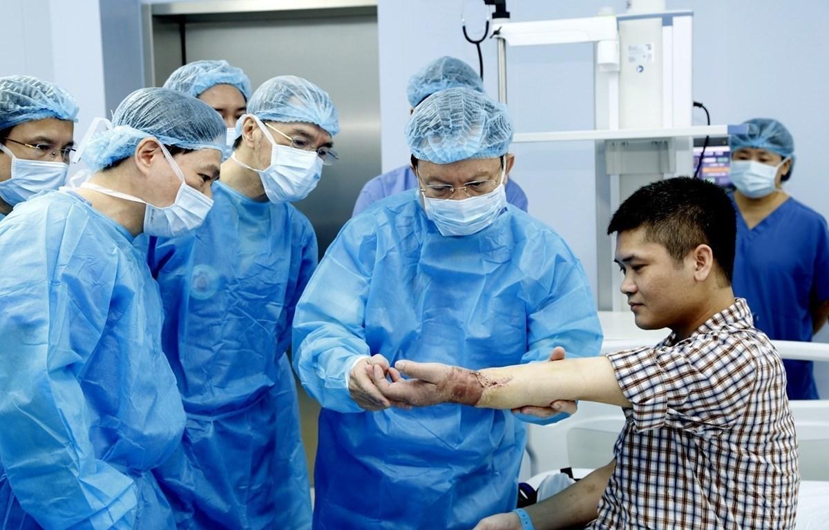 Các y bác sỹ Bệnh viện Trung ương Quân đội 108 kiểm tra tay cho bệnh nhân Vương sau khi ghép. (Ảnh: PV/Vietnam+)