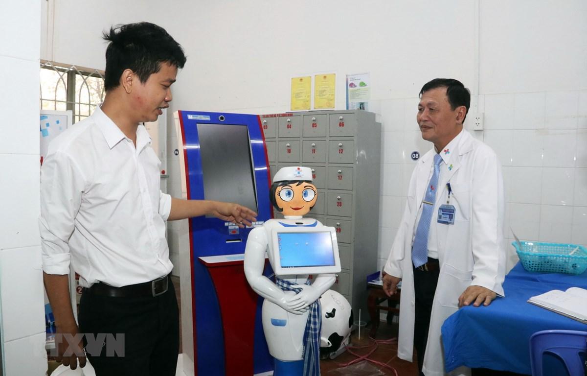 Kỹ sư Võ Hồng Quân, phụ trách Trung tâm Công nghệ thông tin, Bệnh viện Quân dân y miền Đông (trái) giới thiệu robot thông minh Cô Tấm hỗ trợ người bệnh. (Ảnh: Xuân Khu/TTXVN)