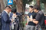 Phóng viên quốc tế ăn bánh mì kẹp, túc trực tác nghiệp trên hè phố
