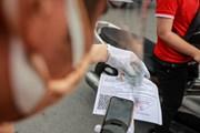 [Photo] Nhiều người dân Hà Nội bắt đầu sử dụng giấy đi đường mới