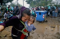 [Photo] Xót xa cảnh người di cư kiệt sức vì dầm mưa
