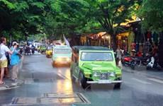 Khách du lịch thích thú ngắm đoàn xe cổ diễu hành ở Hội An
