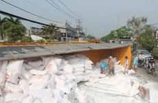 Cua lên dốc, xe container chở 34 tấn bột mỳ mất lái lật xuống đường