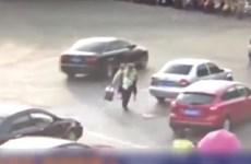 """[Video] Cảnh sát Trung Quốc """"liều mình"""" cõng cụ già qua đường"""