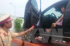 Bị dừng xe do vượt đèn vàng, nữ tài xế cố thủ trong ôtô