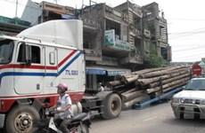 Xe container chở đầy gỗ bất ngờ lật vào nhà dân