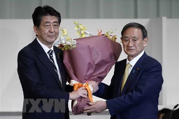 Thủ tướng Nhật Bản sắp mãn nhiệm Shinzo Abe (trái) chúc mừng tân Chủ tịch đảng Dân chủ Tự do (LDP) cầm quyền vừa đắc cử Yoshihide Suga tại Tokyo ngày 14-9-2020. Ảnh: TTXVN phát