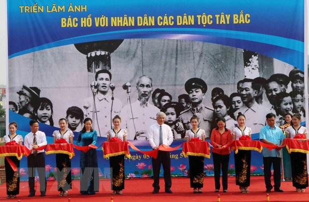 Các vị lãnh đạo tỉnh Sơn La và lãnh đạo Ban Quản lý Di tích Chủ tịch Hồ Chí Minh cắt băng khai mạc triển lãm ảnh 'Bác Hồ với nhân dân các dân tộc Tây Bắc.' (Ảnh: Nguyễn Cường/TTXVN)