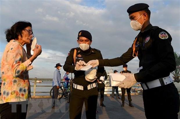 Cảnh sát phát khẩu trang miễn phí cho người dân tại Phnom Penh, Campuchia. Ảnh: AFP/TTXVN