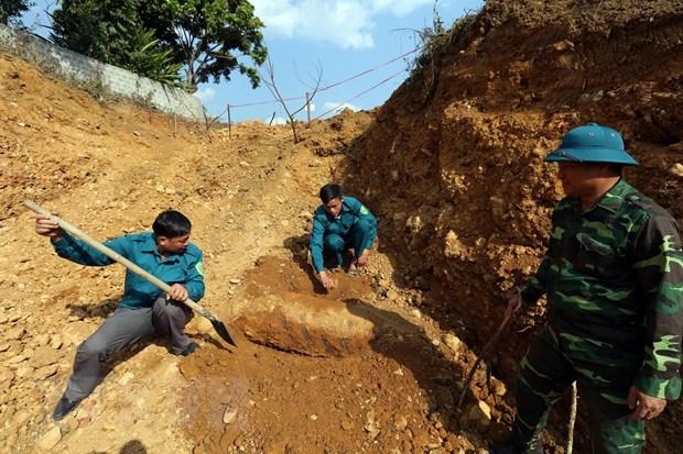 Cán bộ, chiến sỹ Ban Chỉ huy Quân sự thành phố Điện Biên Phủ đang xem xét khả năng hủy nổ an toàn quả bom. (Ảnh: Phan Tuấn Anh/TTXVN)