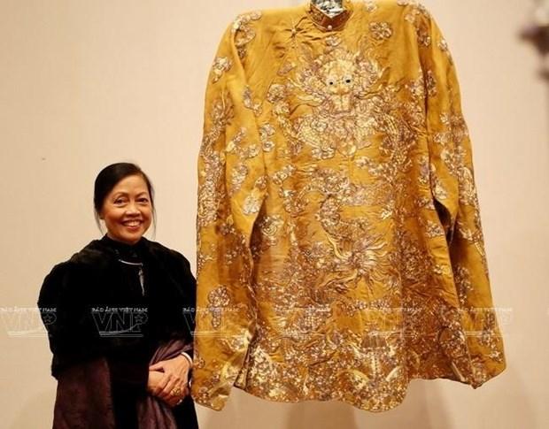 Nhà nghiên cứu Thái Kim Lan bên chiếc long bào của vua Khải Định. (Ảnh: Báo Ảnh Việt Nam/TTXVN)
