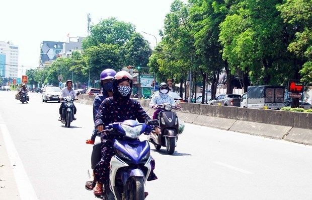 Người dân đều trang bị khẩu trang và mặc áo chống nắng kín khi di chuyển trên đường trong thời tiết nắng nóng. (Ảnh: Tá Chuyên/TTXVN)