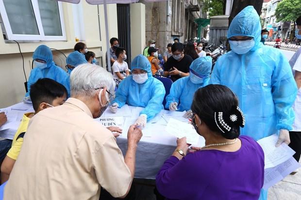 Người về từ Đà Nẵng làm thủ tục xét nghiệm nhanh tại phường Bách Khoa và phường Cầu Dền (quận Hai Bà Trưng) sáng 01/.2020. (Ảnh: Minh Quyết/TTXVN)