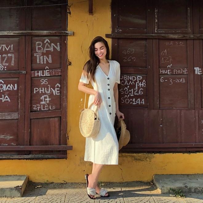 Hồ Ngọc Hà hóa thân thành quý cô Hoài Phố trong chiếc đầm trắng cổ cắt chữ V, thắt eo nhẹ nhàng, duyên dáng. Không chưng diện hào nhoáng hay mang hàng hiệu xa xỉ, ''nữ hoàng giải trí'' vẫn khiến góc phố Hội An sáng bừng bởi vẻ nữ tính, ngọt ngào