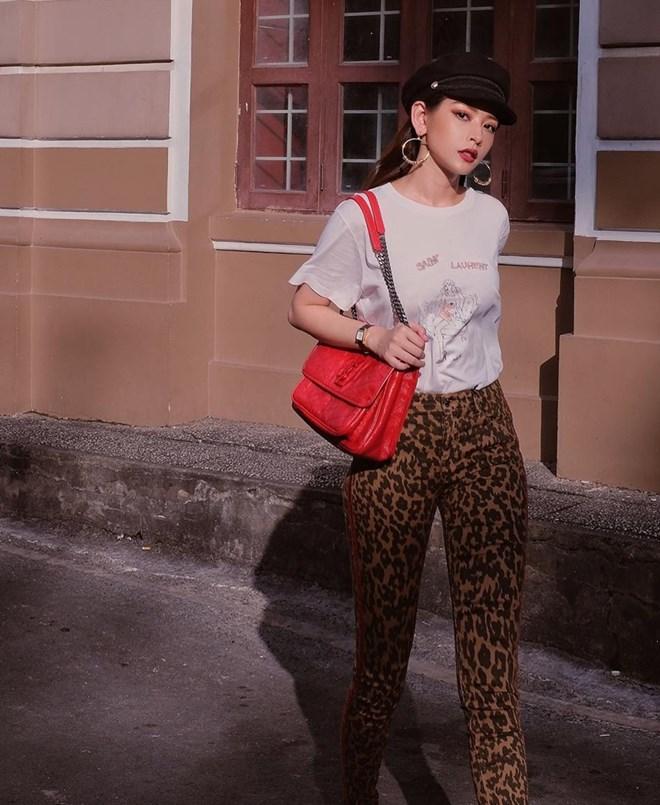 Chi Pu ''chơi trội'' với quần họa tiết da báo, kết hợp áo thun và mũ baker boy cá tính. Chiếc túi Niki da đỏ của Saint Laurent vừa vặn trở thành phụ kiện hoàn thiện phong cách retro cho nàng hot girl đình đám.