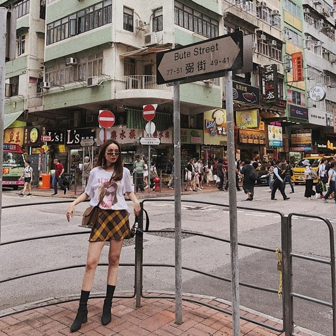 Yến Trang gây ấn tượng với street style cá tính tại Hong Kong. Nữ ca sỹ trưng dụng áo phông họa tiết với chân váy ngắn, mang boots cao gót để tạo hiệu ứng thị giác, khiến chân thon gọn và như dài hơn.