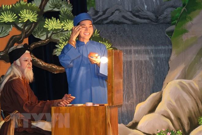 Nghệ sĩ cải lương giới thiệu công đoạn trang điểm của nghệ sĩ trước khi ra  sân khấu biểu diễn. (Ảnh: Gia Thuận/TTXVN)