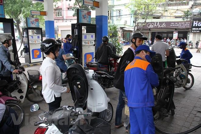 Nhân viên Petrolimex đang bán xăng cho khách hàng. Ảnh: Đức Duy/Vietnam+