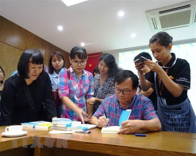 Nhà văn Nguyễn Nhật Ánh tặng chữ ký cho độc giả. Ảnh: Gia Thuận/TTXVN