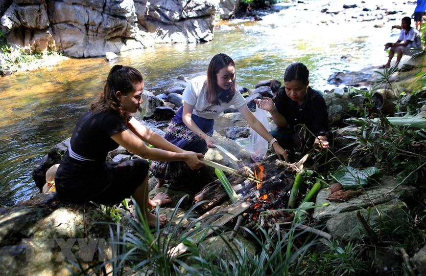 Du khách tự nướng món ăn và thưởng thức bên dòng suối Tà Lao mát lạnh. (Ảnh: Hồ Cầu/TTXVN)