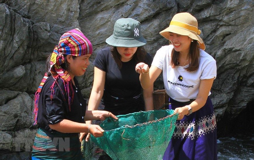 Những thiếu nữ miền xuôi trong bộ trang phục đồng bào dân tộc Vân Kiều trải nghiệm bắt cá ở con suối Tà Lao, xã Tà Long. (Ảnh: Hồ Cầu/TTXVN)