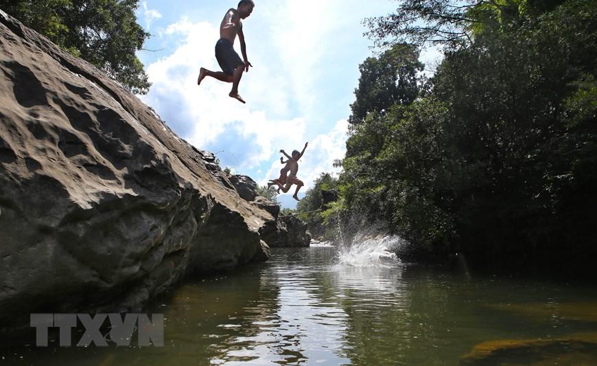 Du khách tắm mát ở con suối Tà Lao, xã Tà Long, trong chuyến du lịch trải nghiệm. (Ảnh: Hồ Cầu/TTXVN)